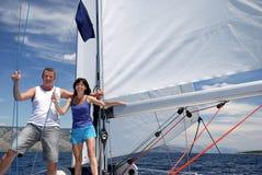 Två lyckliga folk som reser med segelbåten Royaltyfria Foton