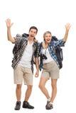 Två lyckliga fotvandrare som vinkar på kameran royaltyfri bild