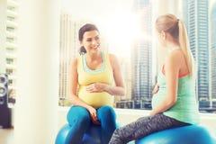 Två lyckliga gravida kvinnor som sitter på bollar i idrottshall Arkivbilder