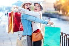 Två lyckliga härliga flickor med omfamning för shoppingpåsar i staden Royaltyfri Foto