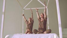 Två lyckliga härliga kvinnor som gör yoga och knastrar till det vänstert och till rätten lager videofilmer