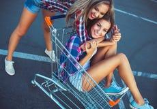 Två lyckliga härliga tonåriga flickor som utomhus kör shoppingvagnen Royaltyfria Foton