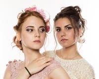 Två lyckliga härliga unga kvinnor i eleganta klänningar, mjuk historia fotografering för bildbyråer