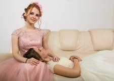 Två lyckliga härliga unga kvinnor i eleganta klänningar, mjuk historia arkivfoto