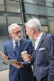 Två lyckliga höga gråa håraffärsmän som promenerar gatan under kaffeavbrott royaltyfri fotografi