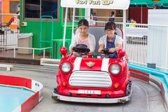 Två lyckliga japanska flickor som rider på en Furi Furi GP-bil på Tokyo D royaltyfria bilder