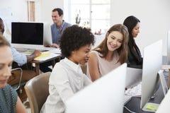 Två lyckliga kvinnor diskuterar arbete på datoren i öppet plankontor Royaltyfri Bild