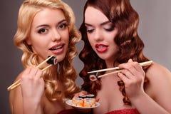 Två lyckliga kvinnor som äter sushirullar Fotografering för Bildbyråer