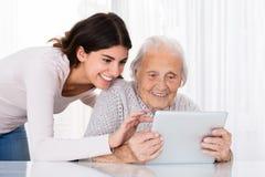 Två lyckliga kvinnor som använder den Digital minnestavlan arkivbild