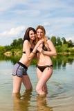 Två lyckliga kvinnor som har gyckel på sjön i sommar Royaltyfria Bilder