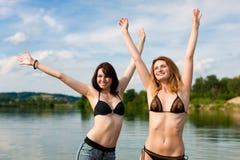 Två lyckliga kvinnor som har gyckel på sjön i sommar Royaltyfri Foto