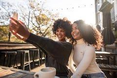 Två lyckliga kvinnor som har gyckel som tar en selfie Royaltyfri Foto