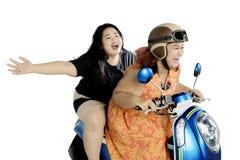Två lyckliga kvinnor som rider en moped på studio Arkivfoton