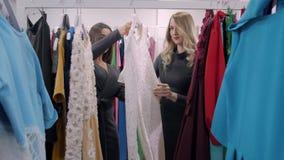 Två lyckliga kvinnor som shoppar i kläder, lagrar, väljer klänningen Blond och arabisk ung flicka arkivfilmer