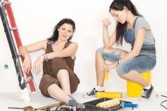 Två lyckliga kvinnor som tar ett avbrott från att dekorera royaltyfri fotografi