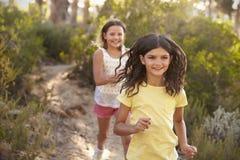 Två lyckliga le flickor som jagar sig i en skog Royaltyfria Foton