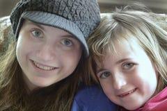 Två lyckliga le framsidor för flickasystrar Arkivfoto
