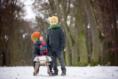 Två lyckliga lilla barn, pojkar som utomhus spelar i snöig, parkerar Arkivfoto