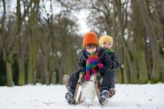 Två lyckliga lilla barn, pojkar som utomhus spelar i snöig, parkerar Arkivbild