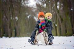 Två lyckliga lilla barn, pojkar som utomhus spelar i snöig, parkerar Royaltyfri Fotografi