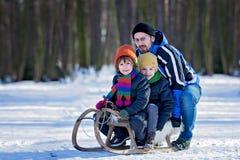 Två lyckliga lilla barn, pojkar som utomhus spelar i snöig, parkerar Arkivbilder