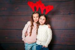 Två lyckliga lilla le flickor Julfilial och klockor Le roliga systrar i hjorthorn i studio Arkivfoto