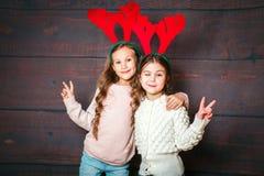 Två lyckliga lilla le flickor som har gyckel Julfilial och klockor Le roliga systrar i hjorthorn på träbakgrund Arkivbilder