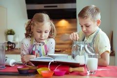 Två lyckliga lilla och gulliga barn som förbereder muffin i modernt K Royaltyfria Foton