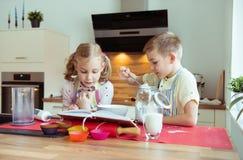 Två lyckliga lilla och gulliga barn som förbereder muffin i modernt K Royaltyfri Foto