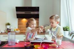 Två lyckliga lilla och gulliga barn som förbereder muffin i modernt K Arkivfoto