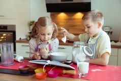 Två lyckliga lilla och gulliga barn som förbereder muffin i modernt K Arkivbilder