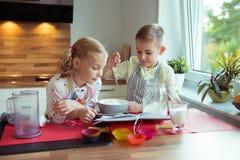 Två lyckliga lilla och gulliga barn som förbereder muffin i modernt K Royaltyfria Bilder