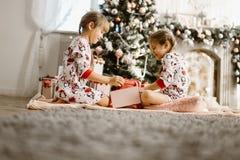 Två lyckliga lilla systrar i pyjamas sitter på mattan och öppnar det nya årets gåvor i det ljusa hemtrevliga rummet med här fotografering för bildbyråer