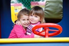 Två lyckliga liten flicka som omfamnar på playgroung Arkivfoton