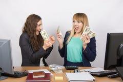 Två lyckliga lyckliga hållande buntar för kontorsflicka av pengar i deras händer arkivfoto