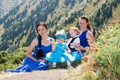 Två lyckliga mammor och barn flicka och pojke som kramar på naturen Arkivbild