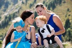 Två lyckliga mammor och barn flicka och pojke som kramar på naturen Fotografering för Bildbyråer