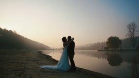 Två lyckliga nygifta personer har sött samtal och att kyssa på aftonen av bröllopdagen på den romantiska sjön på solnedgången arkivfilmer