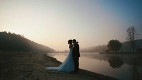 Två lyckliga nygifta personer som omfamnar på aftonen av bröllopdagen på den romantiska sjön på solnedgången stock video