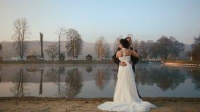 Två lyckliga nygifta personer som omfamnar på aftonen av bröllopdagen på sjön för bergsemesterort på solnedgången lager videofilmer