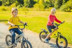 Två lyckliga pojkar som cyklar i, parkerar arkivfoton