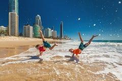 Två lyckliga pojkar som gör handen, står på den Gold Coast stranden, Australien Arkivfoto