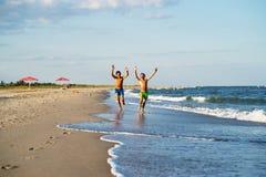 Två lyckliga pojkar som kör på havet, sätter på land på sommar med lyftt ar Arkivfoton