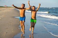 Två lyckliga pojkar som kör på havet, sätter på land på sommar med lyftt ar Royaltyfria Bilder