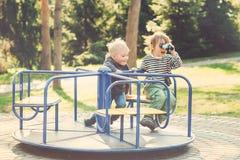 Två lyckliga pojkar som spelar på lekplats i en parkera tonat fotografering för bildbyråer