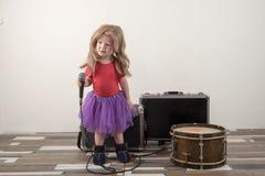 Två lyckliga pyser i smart kläder sjunger en sång med en hemmastadd mikrofon Förbereda sig för julkaraoken royaltyfria foton