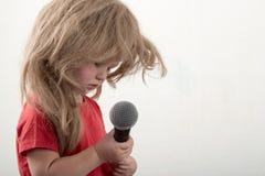 Två lyckliga pyser i smart kläder sjunger en sång med en hemmastadd mikrofon Förbereda sig för julkaraoken Arkivbild