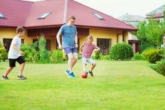 Två lyckliga söner som spelar fotboll med deras fader i trädgårds- near royaltyfria bilder