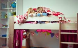 Två lyckliga siblingbarn som har gyckel i britssäng arkivbild