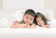 Två lyckliga siblingbarn som ligger under filten arkivfoton